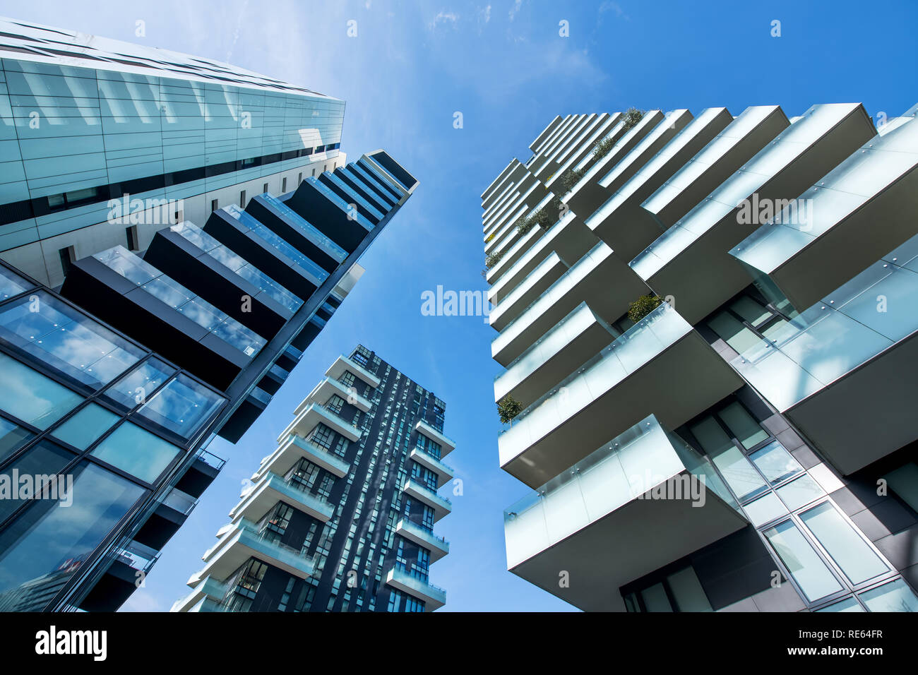 Low angle converging perspective of modern Milan skyscrapers with large balconies against a clear sunny blue sky - Stock Image