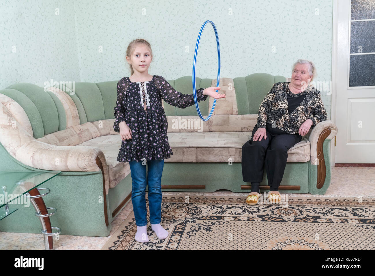 Granddaughter rotates the hoop on the arm, in front of her great-grandmother, sitting on the couch - Stock Image