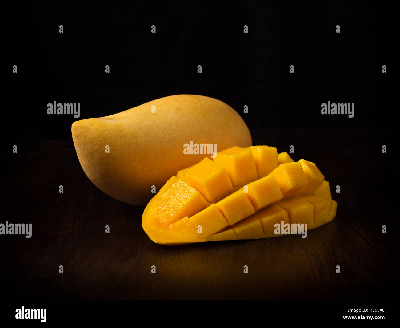 Side view image of close up appetizing yellow mango fruit and mango cubes on wooden table on black backbround Stock Photo