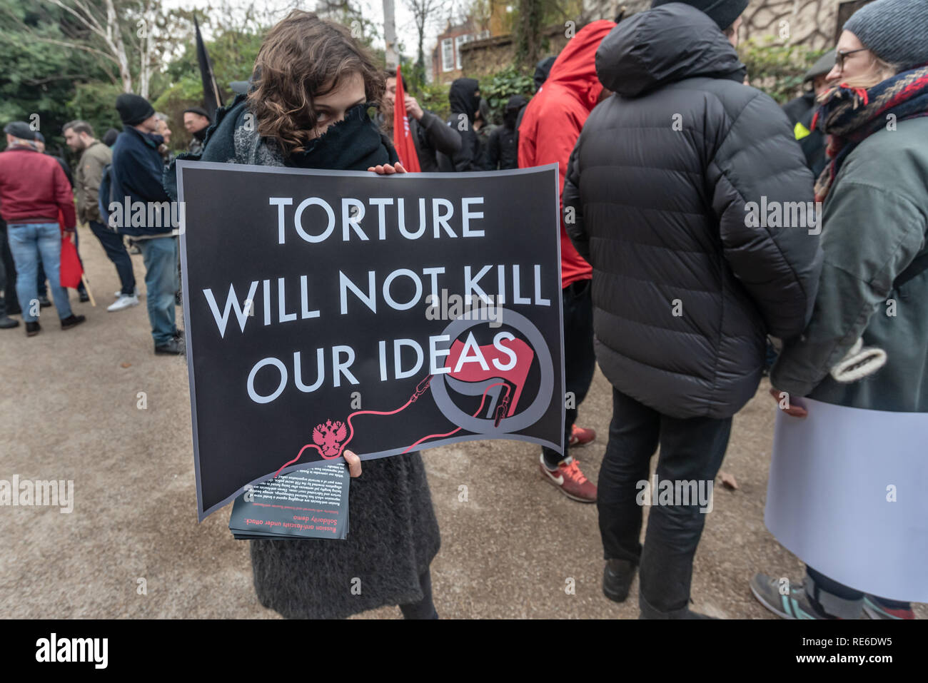 London, UK. 19th January 2019. An anti-fascist holds a poster 'Torture WIll Not Kill Our Ideas' at the Cable St rally to oppose Stanislav Markelovracism, xenophobia, fascism and the upsurge of far-right populism and to show solidarity with Russian anti-fascists who have been arrested, framed and tortured in a brutal wave of repression.  jail for five to twenty years. The rally took place on the anniversary of the brutal murder on the street by fascists of two Russian anti-fascist Credit: Peter Marshall/Alamy Live News - Stock Image