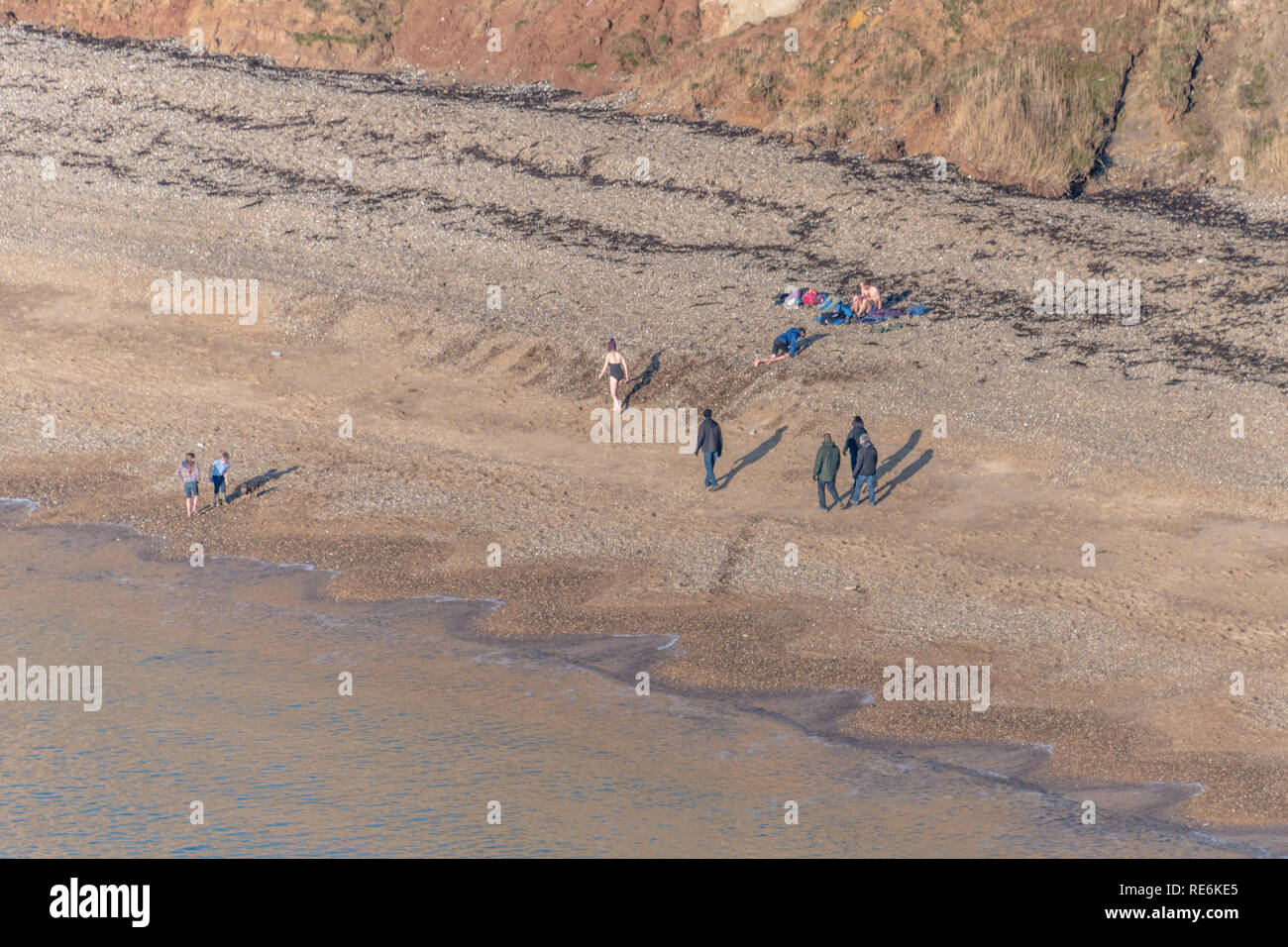 Wareham, UK. Sunday 20th January 2019. Visitors enjoy the winter sun at Worbarrow Beach on the Jurassic Coast in Dorset. People are wrapped up warm in the 4 degree cold but sunny weather. Credit: Thomas Faull/Alamy Live News Stock Photo