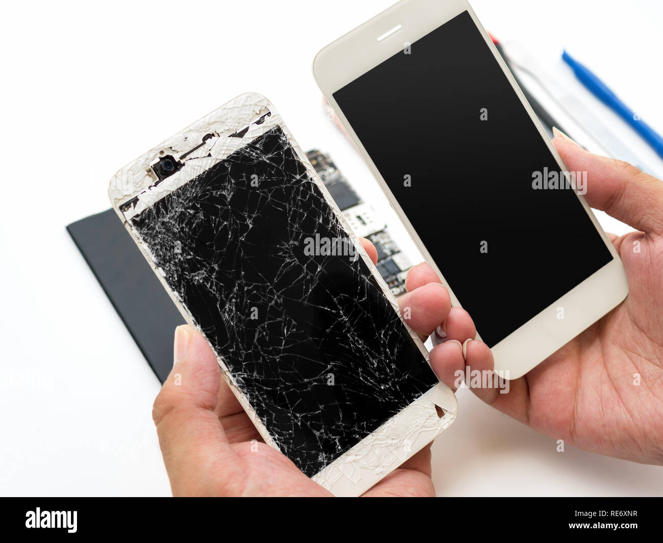 Close-up of cracked smartphone screen compare with new screen in technician hand on blurred smartphone component background - Stock Image