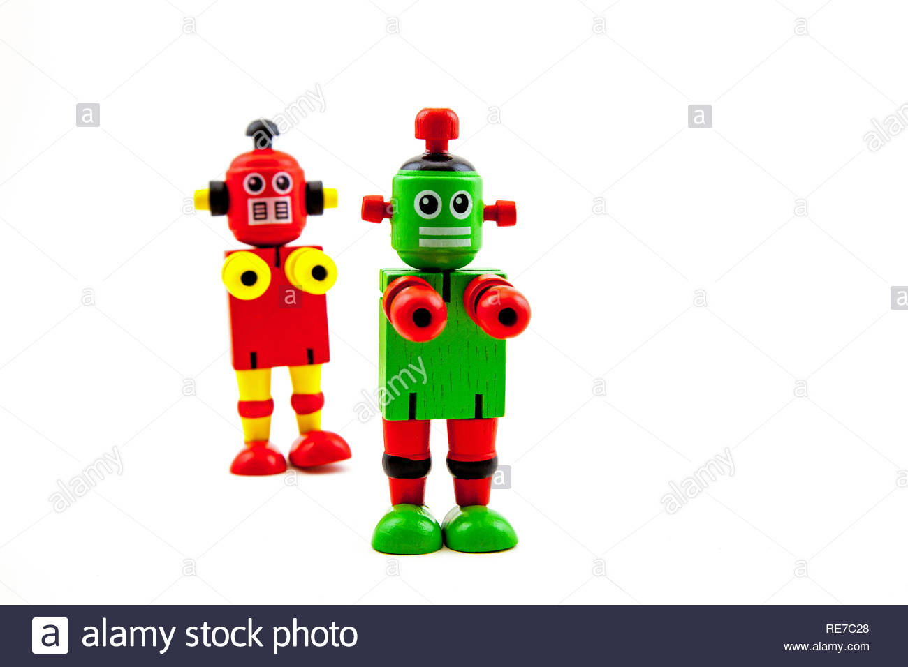 2 wooden toy robots: red/yellow behind (out of focus) and green/red to the front, reaching forward and staring ahead. Copy space on a white background - Stock Image