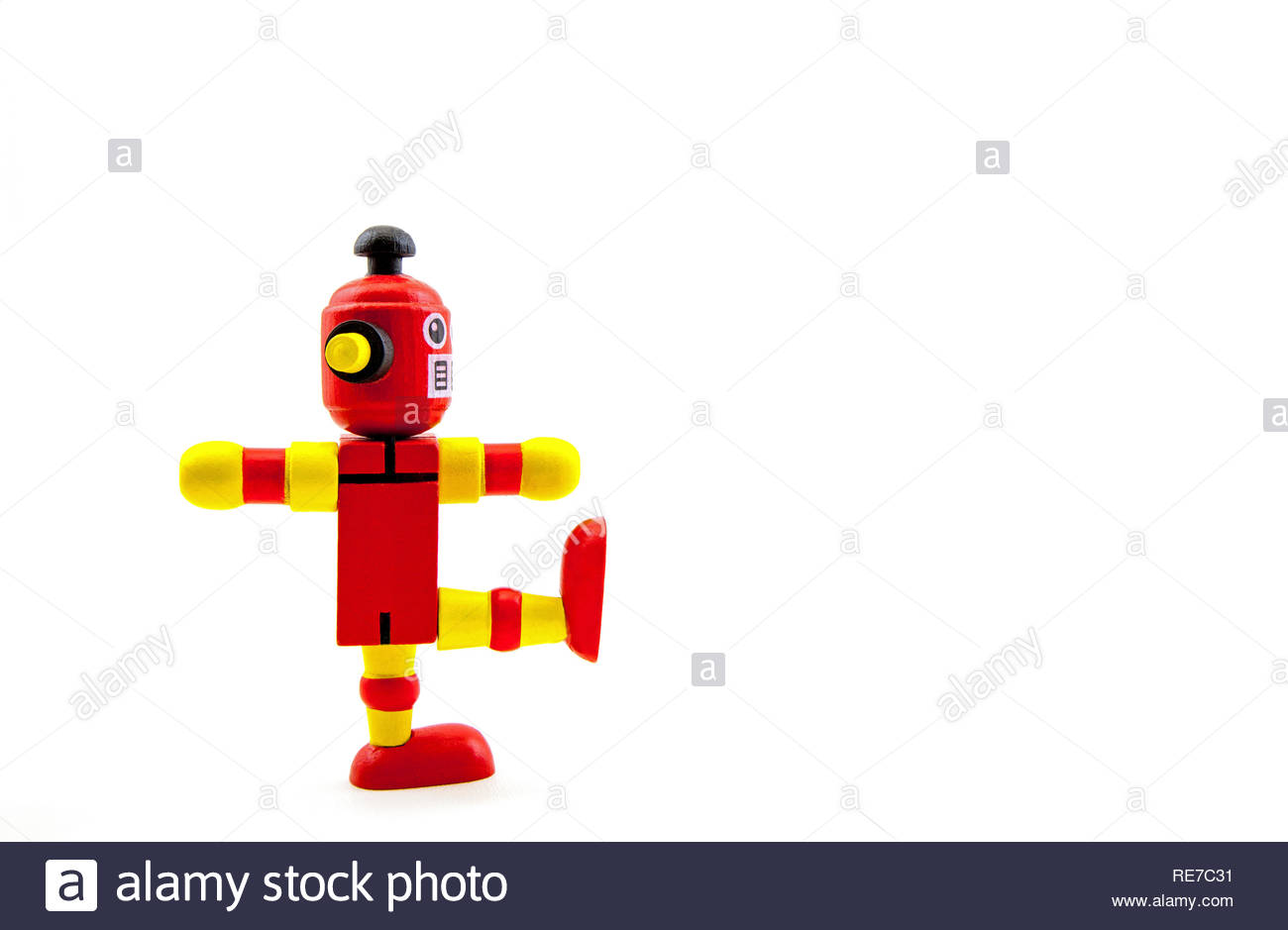 A red / yellow wooden toy robot balancing on one leg as if marching from left to right. Concepts: humour, military, exercise, ahead. White copy space - Stock Image