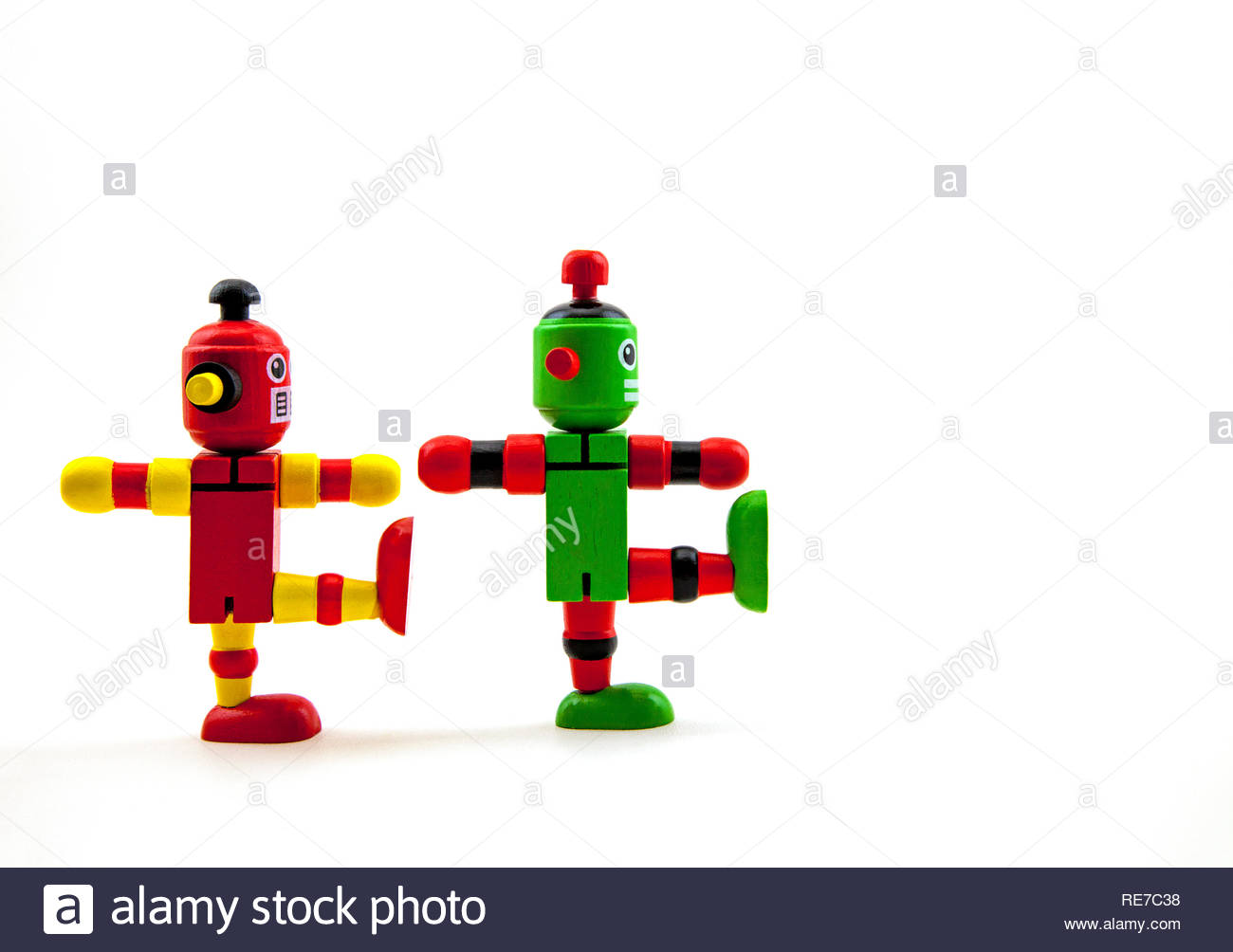2 wooden toy robots, red / yellow & green / red, balancing on one foot, as if marching from left to right. Humour / funny. White background copy space - Stock Image