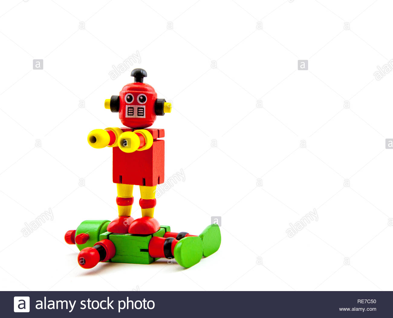 A red / yellow toy wooden robot standing triumphantly on top of a green / red one. copy space Concepts: victory, menace, spite, domination, violence, - Stock Image