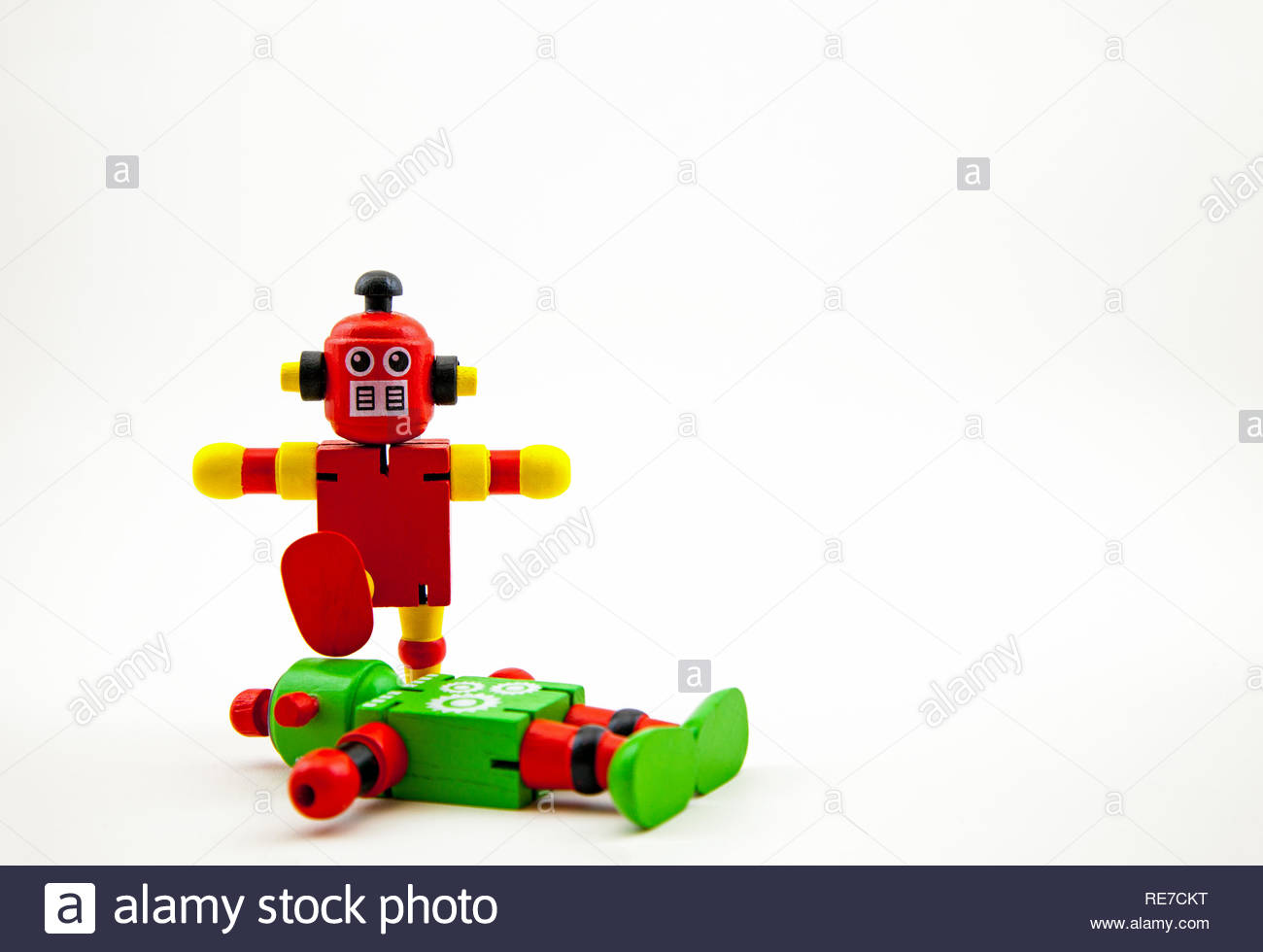 A red/yellow wooden toy robot about to stamp on the head of a prostrate green/red one. White background with copy space. Concepts: violence, menace - Stock Image