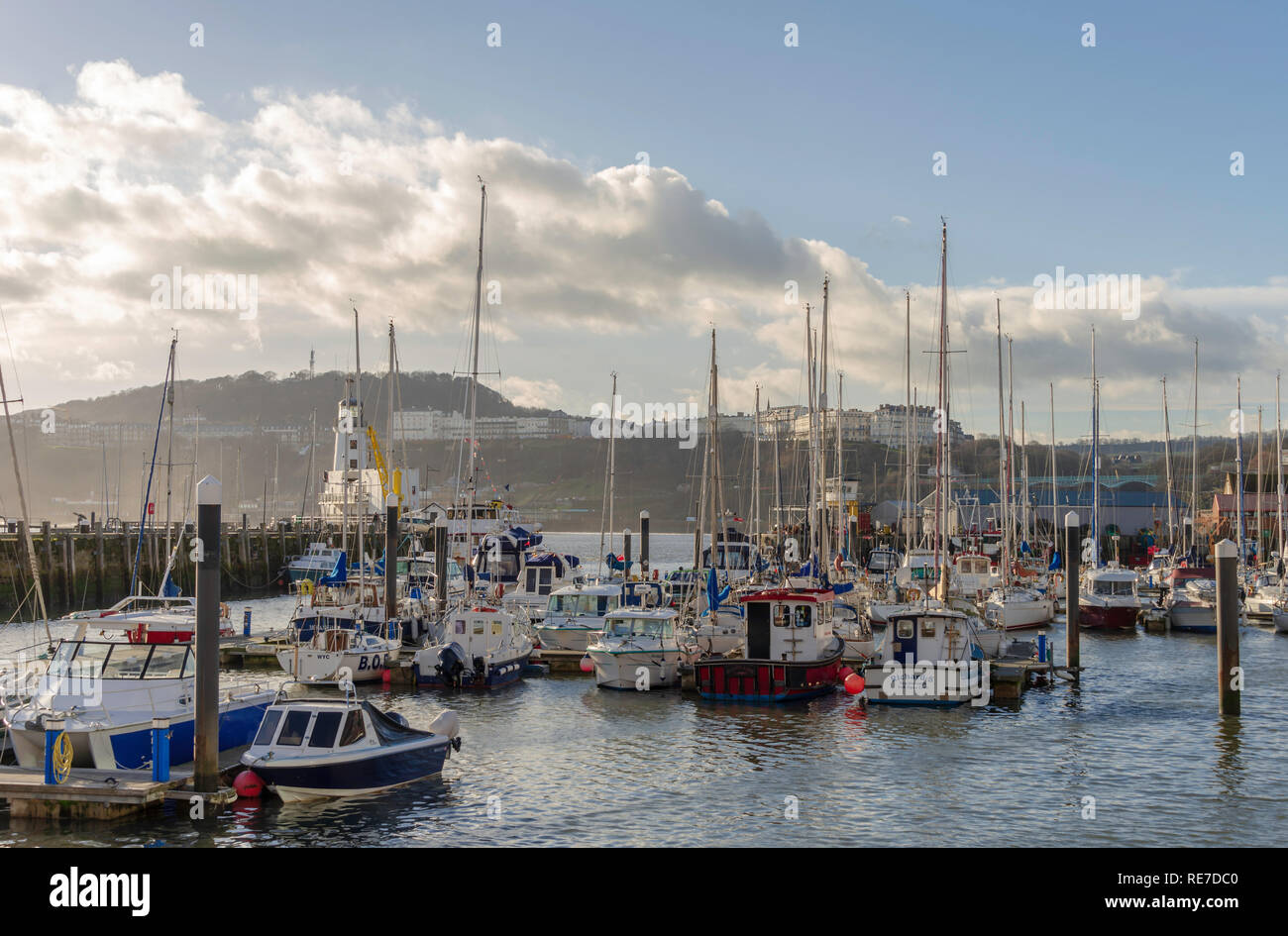 The harbour and marina at Scarborough.  The various boats are moored together and a wharf lies beyond. A lighthouse is to one side and hotels top the  - Stock Image