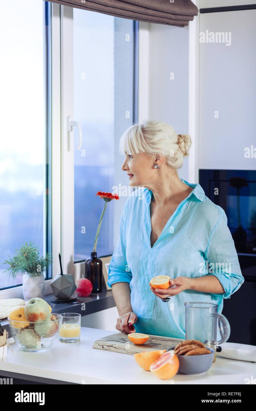 Joyful aged woman looking into the kitchen window - Stock Image
