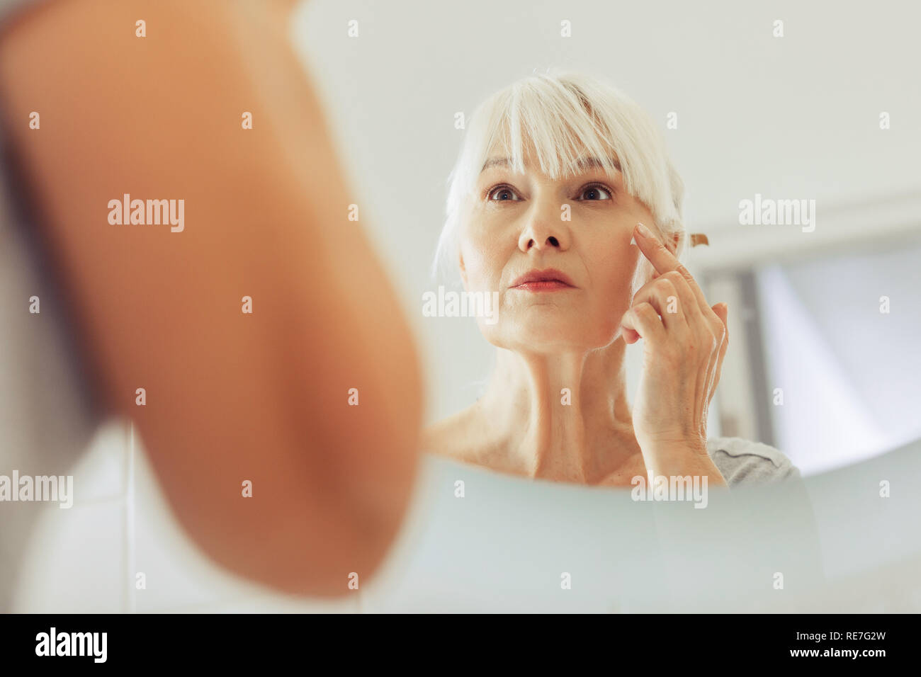 Mirror reflection of a nice aged woman - Stock Image