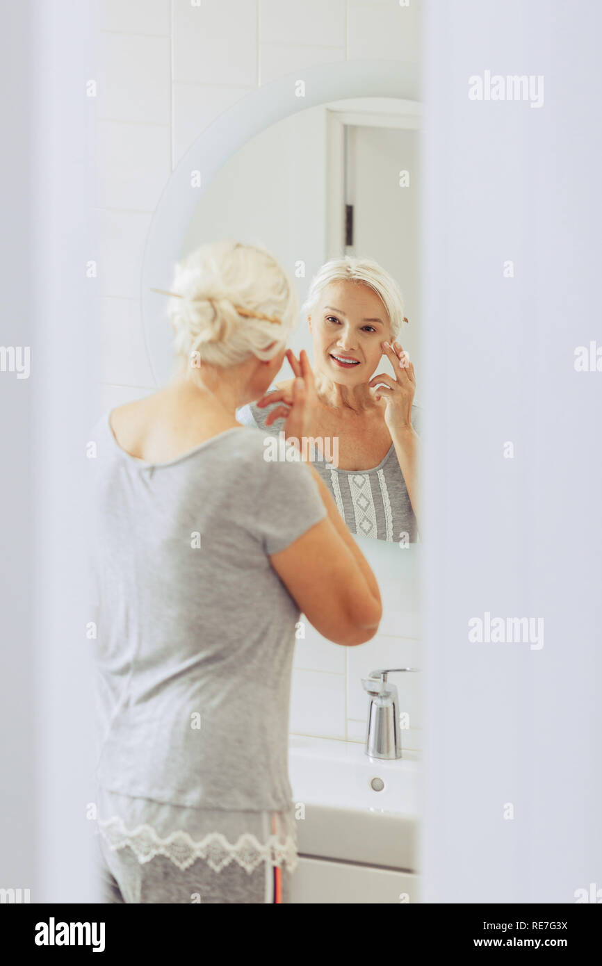 Joyful pleasant woman standing near the sink - Stock Image