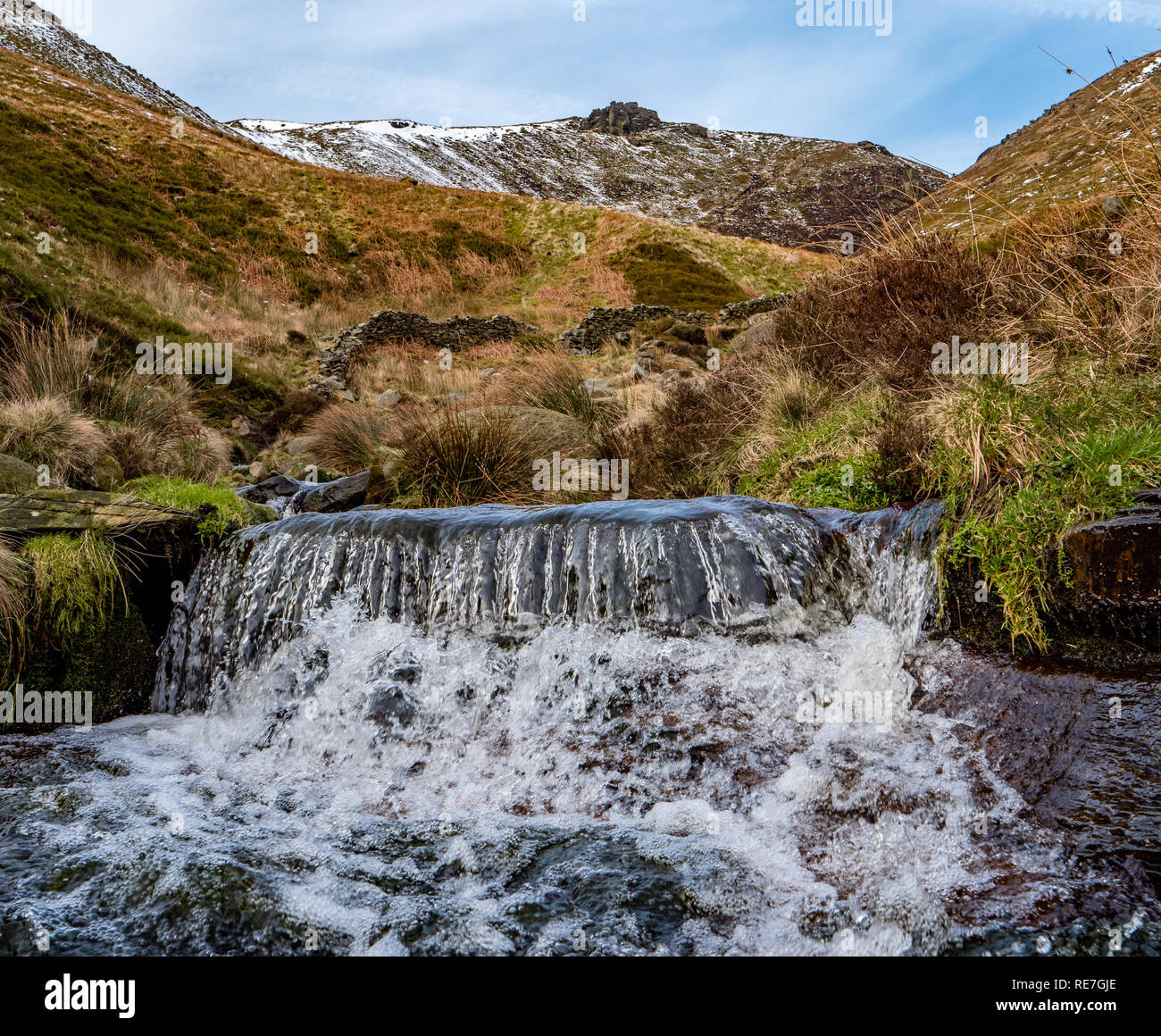 Crowden Tower on the edge of Kinder Scout in the Derbyshire Peak District from the rushing river of Crowden Brook - Stock Image