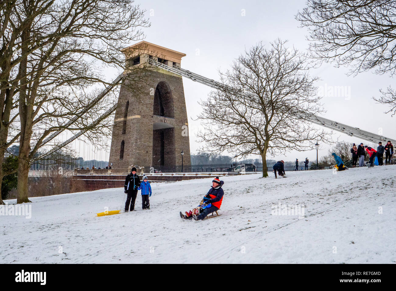 Families enjoying the opportunity of winter snow to sledge down Sion Hill by the Clifton Suspension Bridge Bristol UK Stock Photo