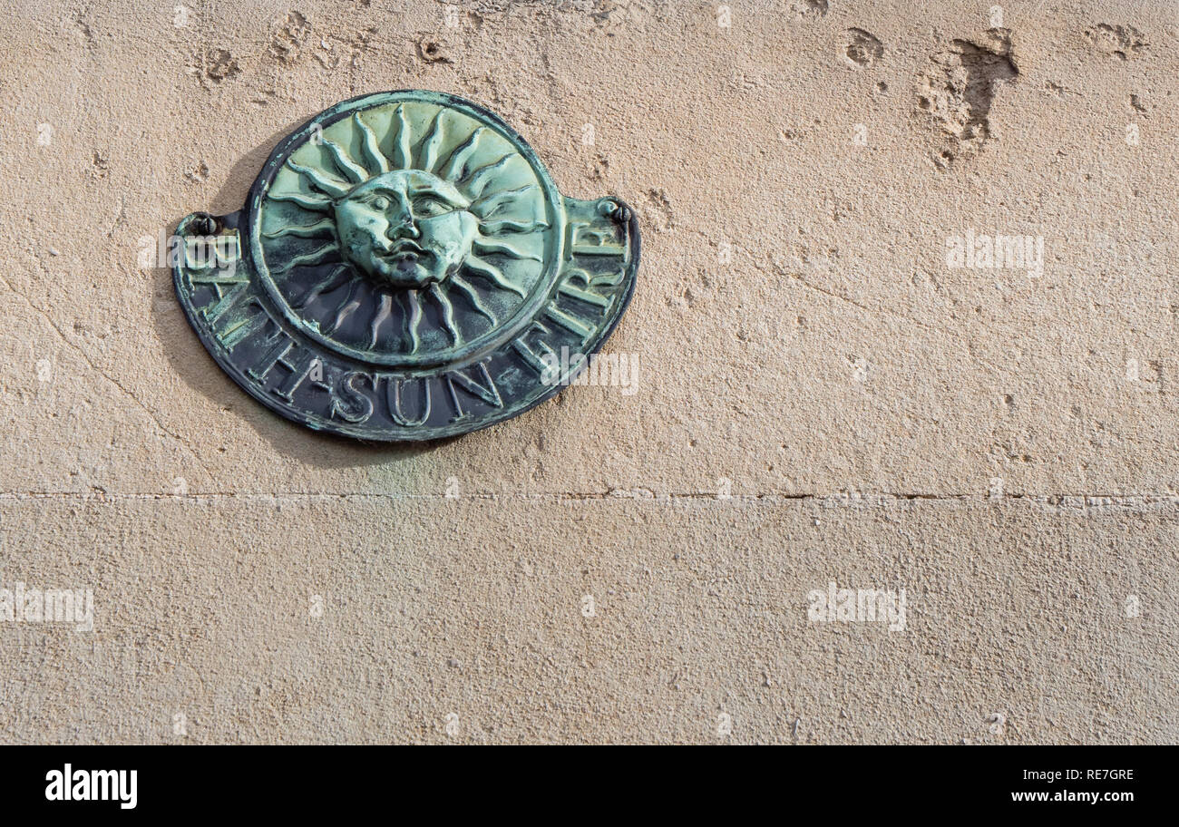 Bronze Bath Sun Fire insurance plaque on the wall of a Georgian stone building in Bath Somereset UK - Stock Image