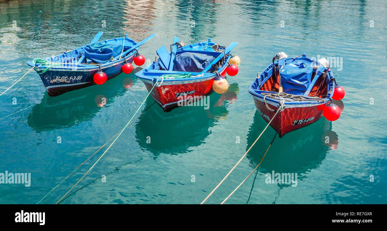 Three rowing boats moored in a harbour on Tenerife in the Canary Islands - Stock Image