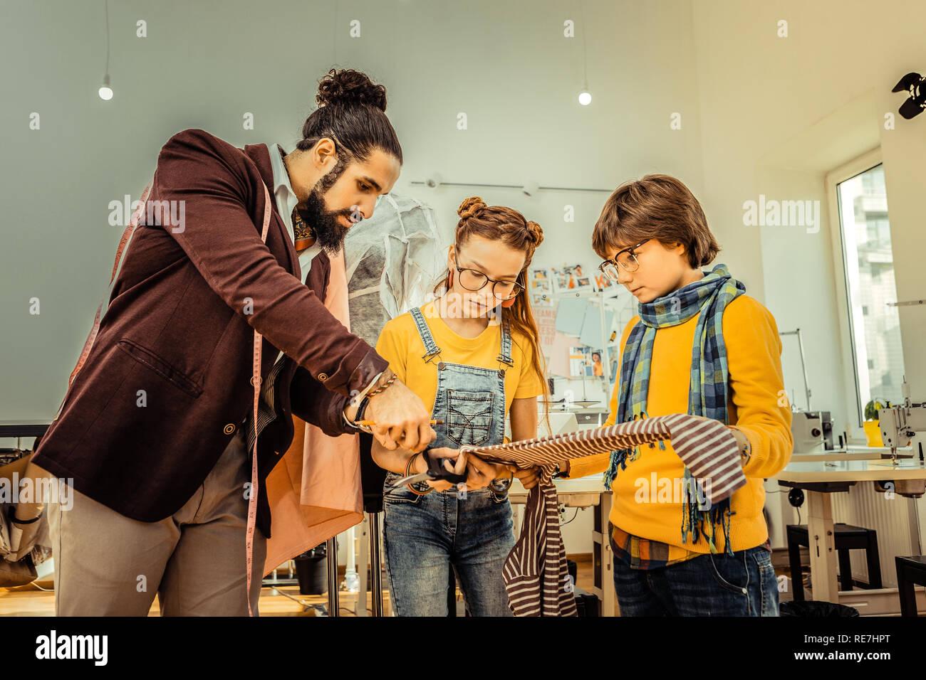 Bearded Fashion Designer Teaching Children Cutting Fabric Stock Photo Alamy