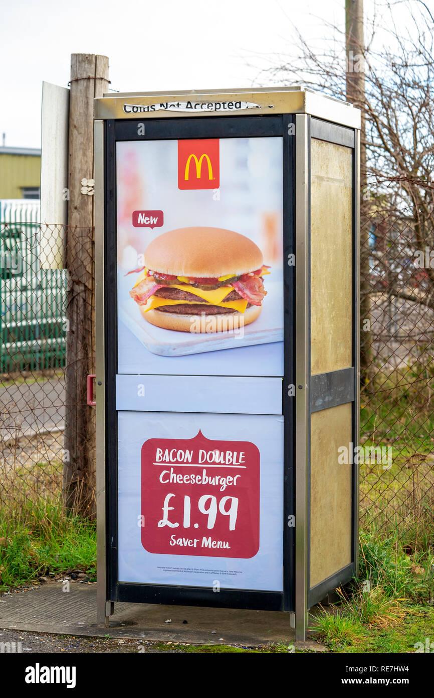 UK telephone kiosk advertising for Mcdonald's burger takeaway restaurant - Stock Image