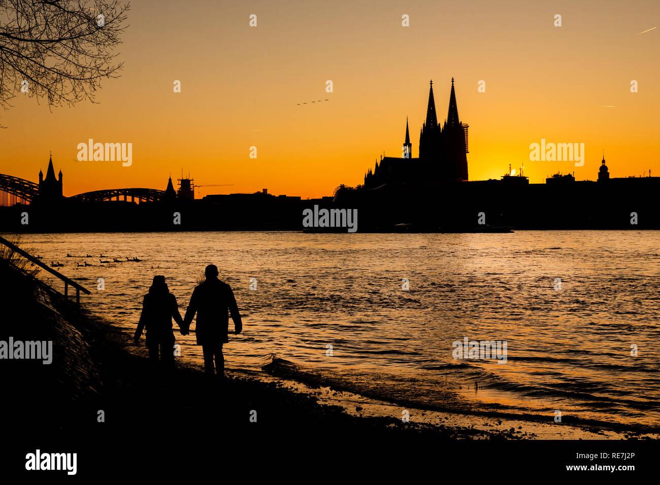 Ein Paar spaziert bei Sonnenuntergang am Ufer des Rheins. Im Hintergrund zeichnet sich der Kölner Dom ab. - Stock Image
