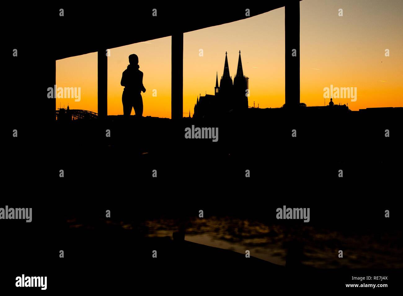 Eine Frau joggt bei Sonnenuntergang durch eine Unterführung am Rhein. Im Hintergrund zeichnet sich der Kölner Dom ab. - Stock Image