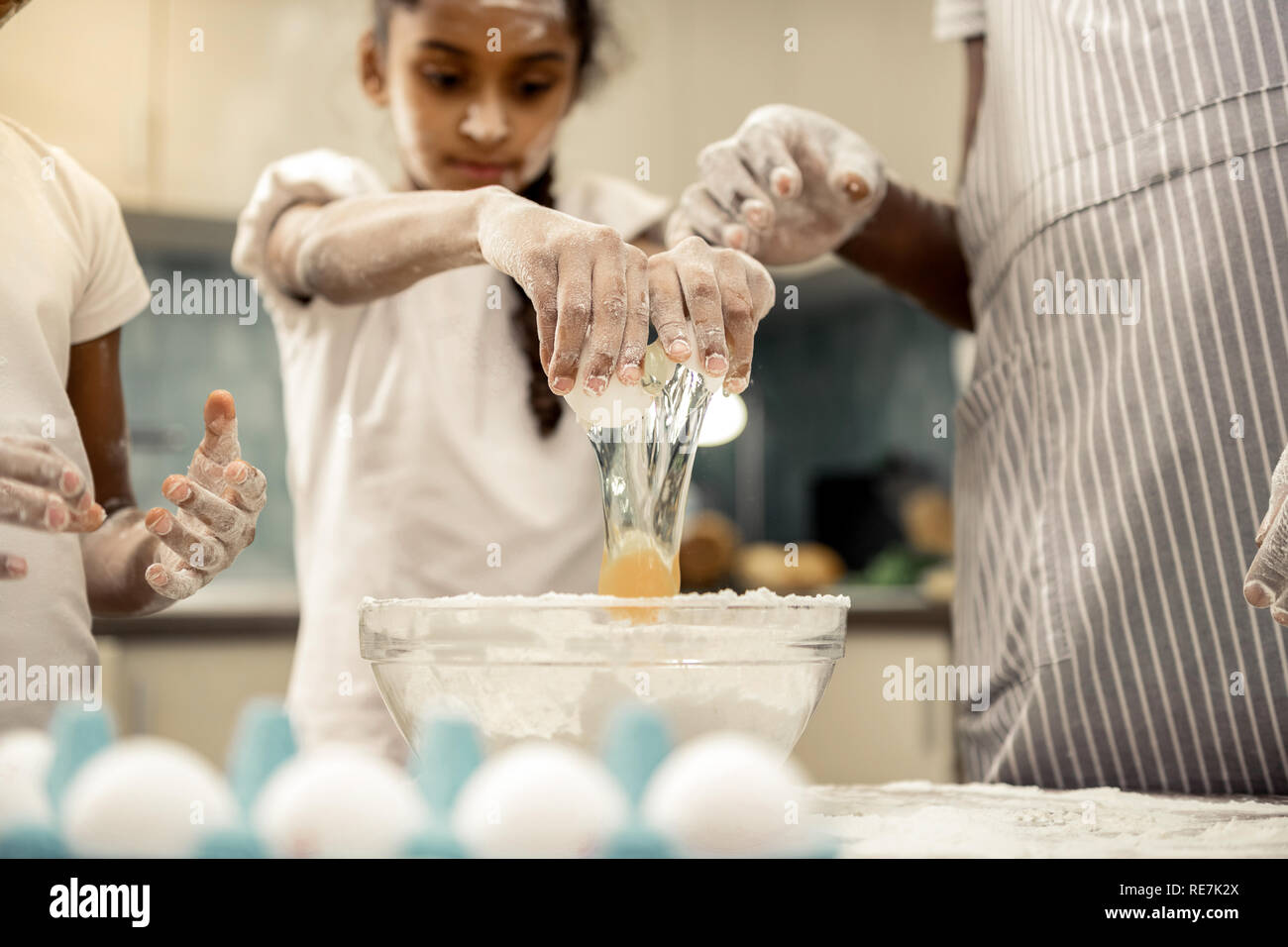 Cute dark-haired daughter beating egg cooking with father - Stock Image