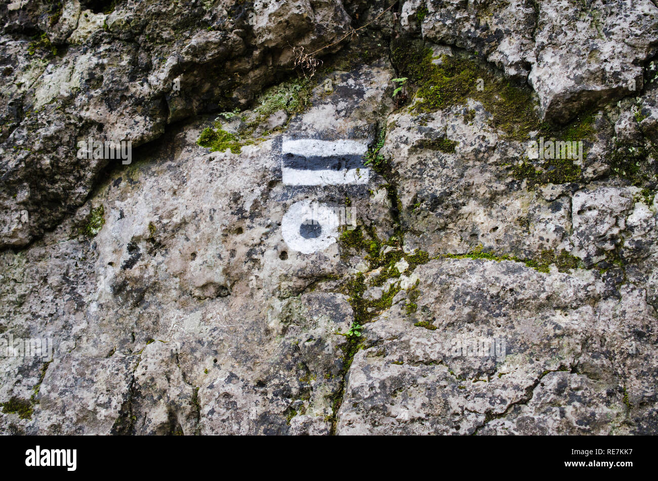Marking the tourist route painted on the stone. Travel route sign. Season of the autumn. - Stock Image