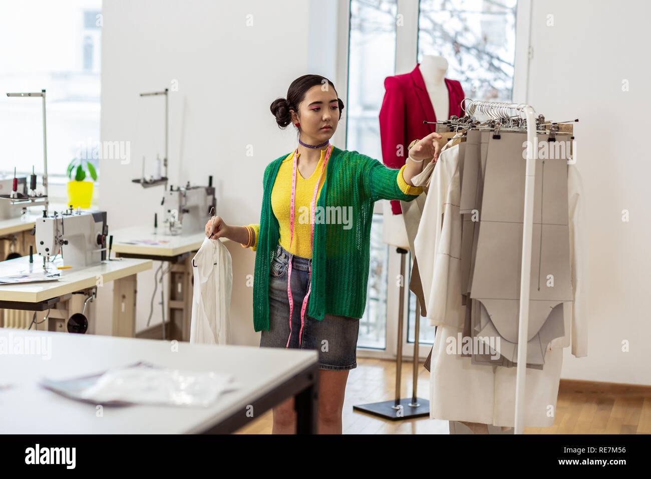 Young Slim Asian Fashion Designer In A Short Skirt Looking At The Dress Patterns Stock Photo Alamy