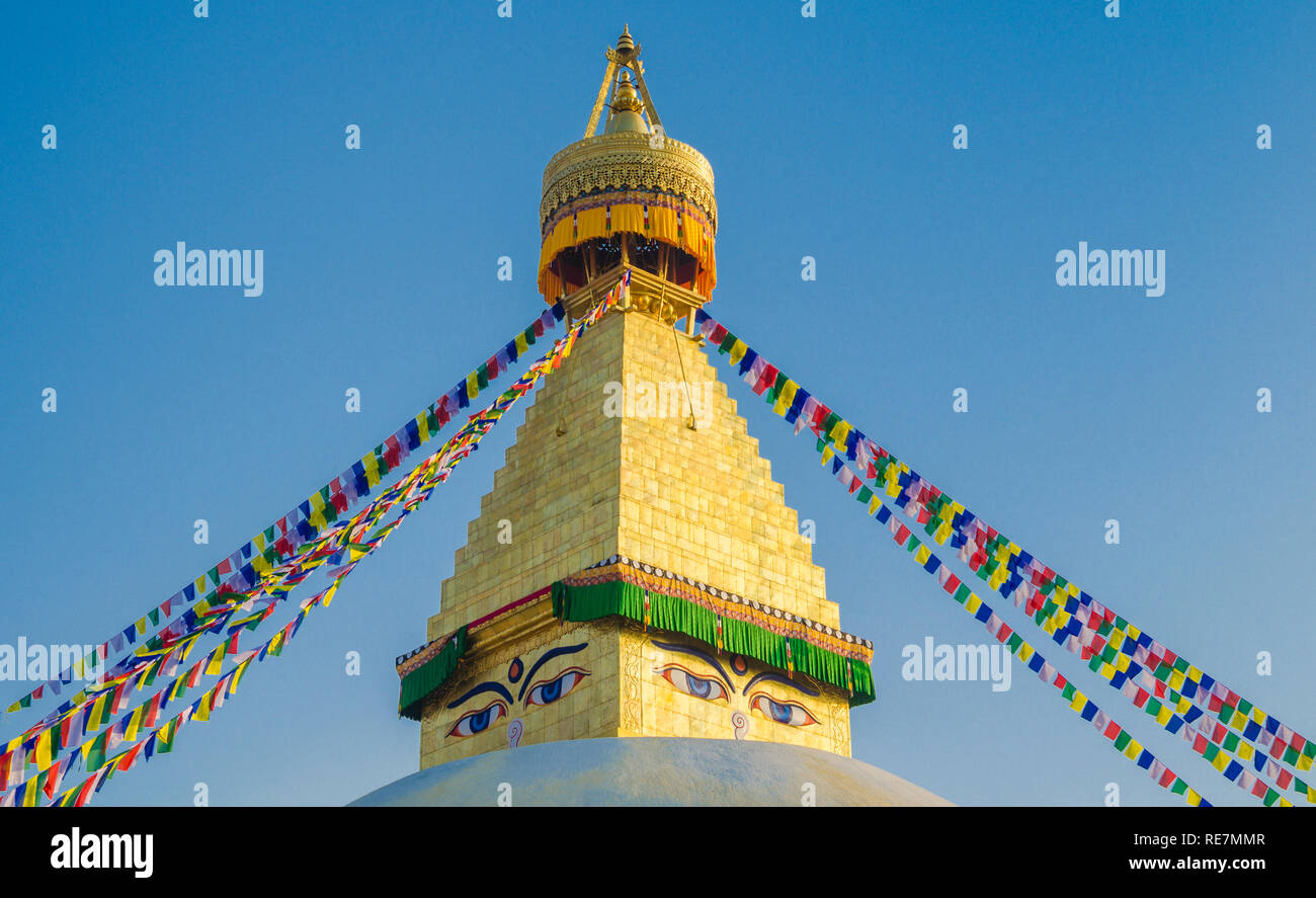 The dome and gold spire of Bodhnath Stupa, Kathmandu, Nepal, with Buddhist prayer flags. - Stock Image