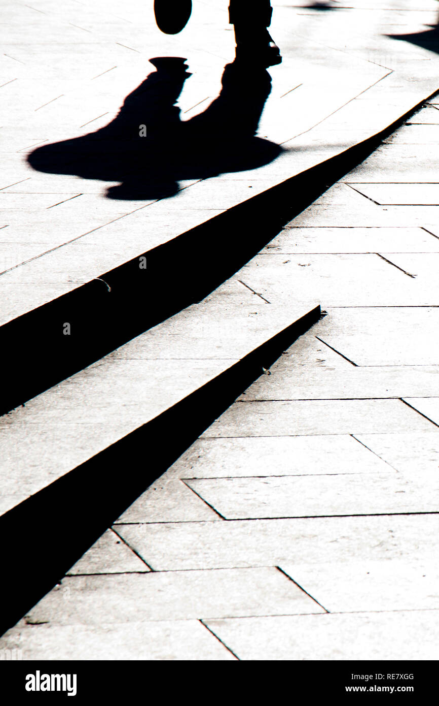 Blurry silhouette shadow of a man walking on a city sidewalk with steps  in black and white high contrast Stock Photo