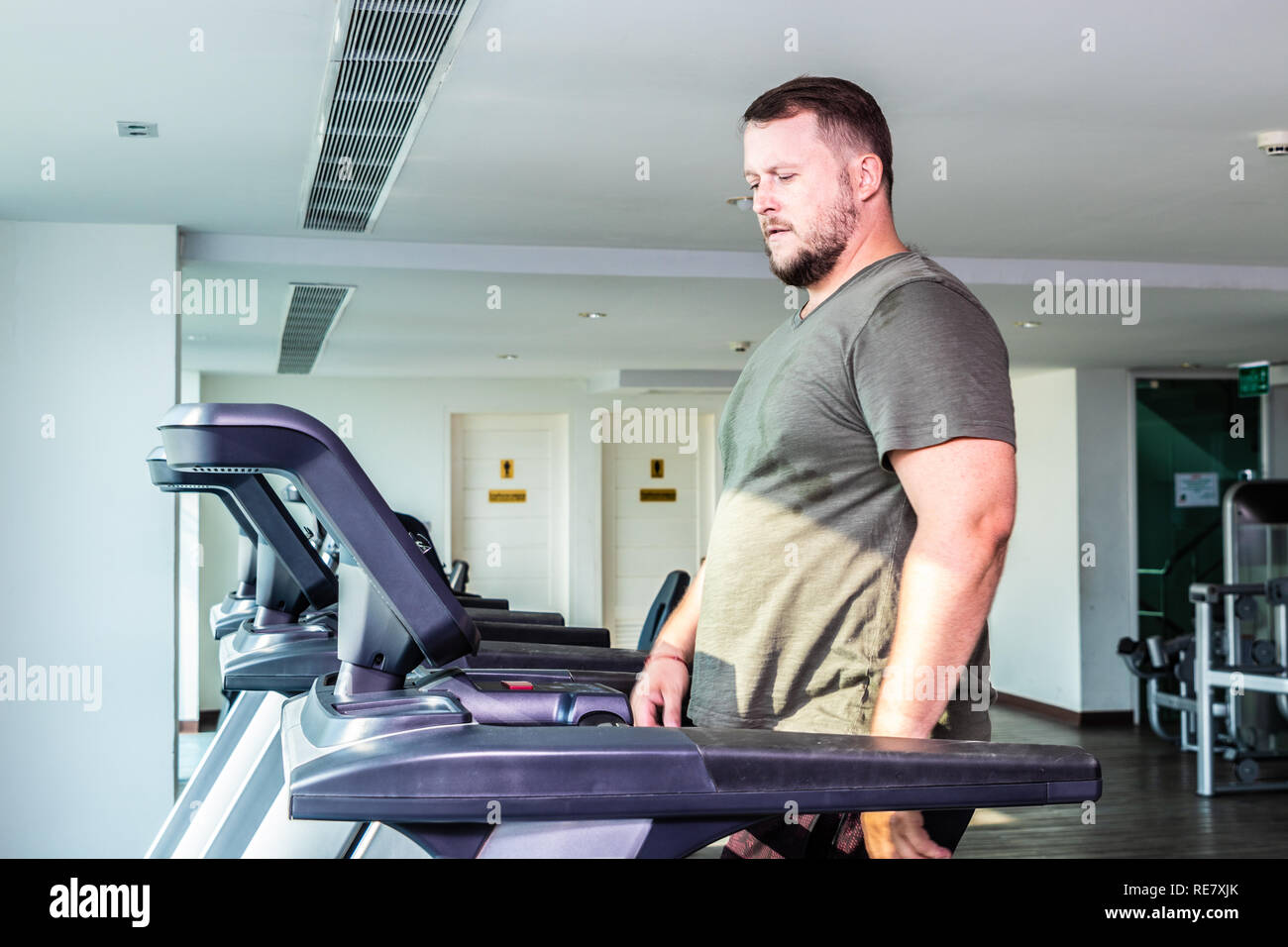 Sweating chubby man walking on running track, warming up on gym treadmill - Stock Image