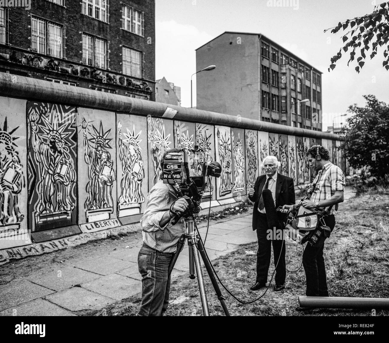 August 1986, CBS TV crew conducting an interview in front of Berlin Wall decorated with Statue of Liberty frescos, West Berlin side, Germany, Europe, - Stock Image