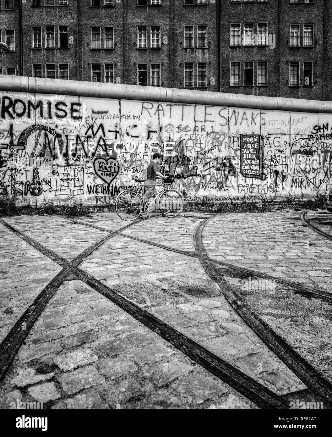 August 1986, Berlin Wall graffitis, tram track ending into wall, cyclist, East Berlin building, West Berlin side, Germany, Europe, - Stock Image