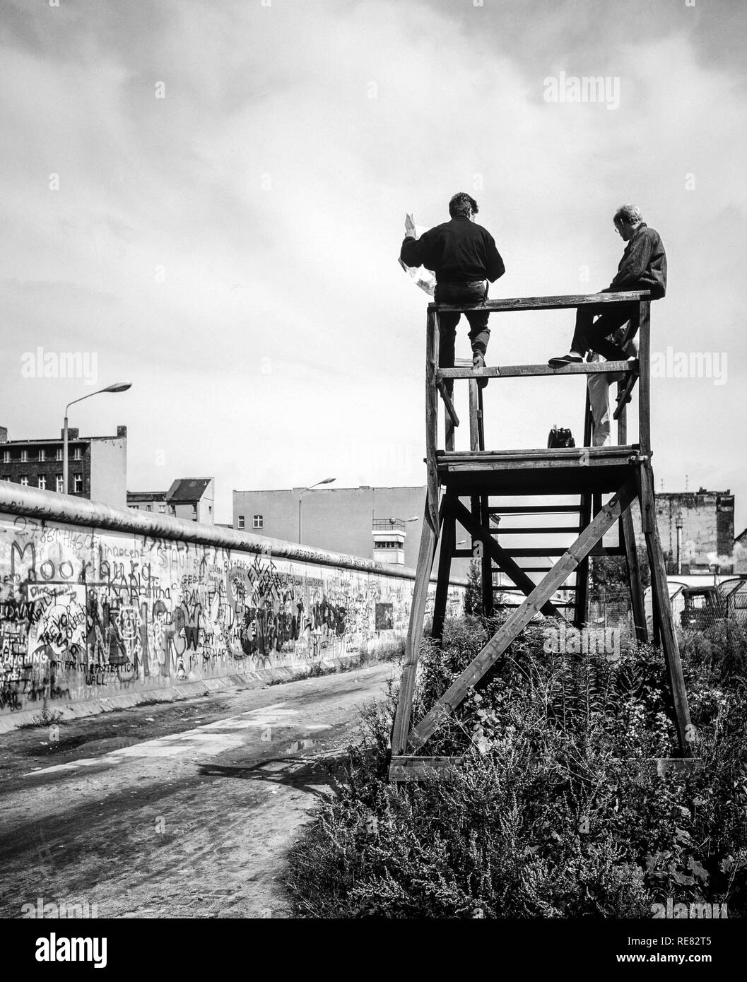 August 1986, Berlin Wall graffitis, people on observation platform looking over the Wall, Zimmerstrasse street, West Berlin side, Germany, Europe, - Stock Image