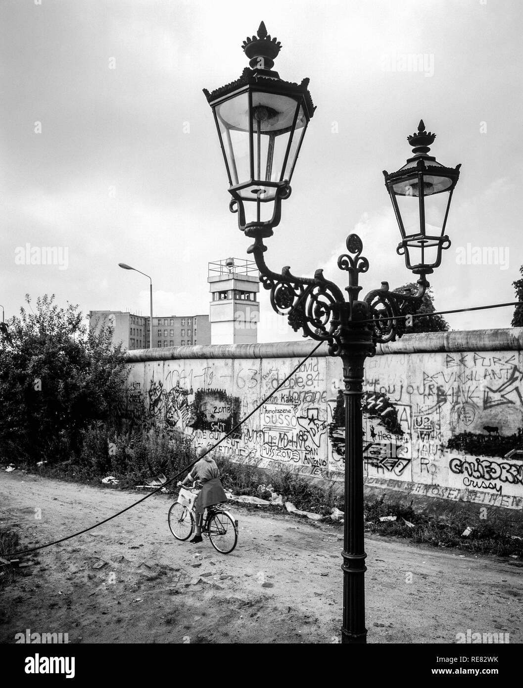 August 1986, Berlin Wall graffitis, street lamp, cyclist, East Berlin watchtower, Zimmerstrasse street, Kreuzberg, West Berlin side, Germany, Europe, - Stock Image