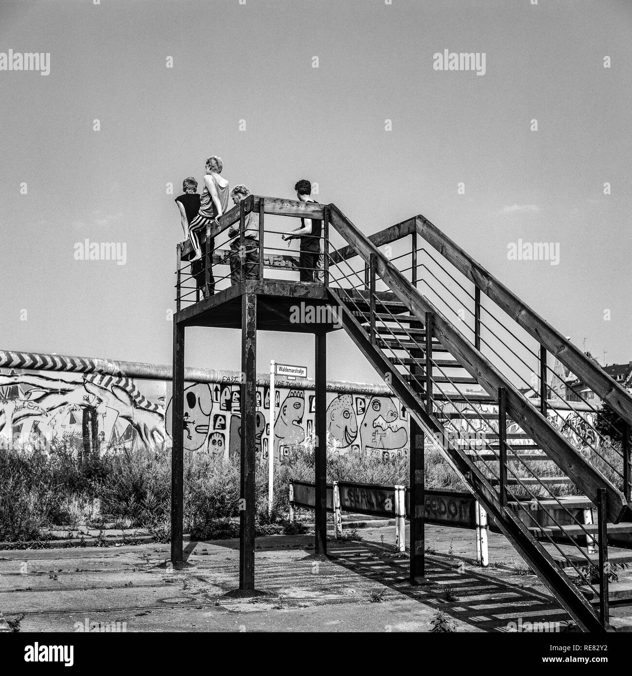 August 1986, Berlin Wall graffitis, four young people on observation platform looking over the Wall, Kreuzberg, West Berlin side, Germany, Europe, - Stock Image