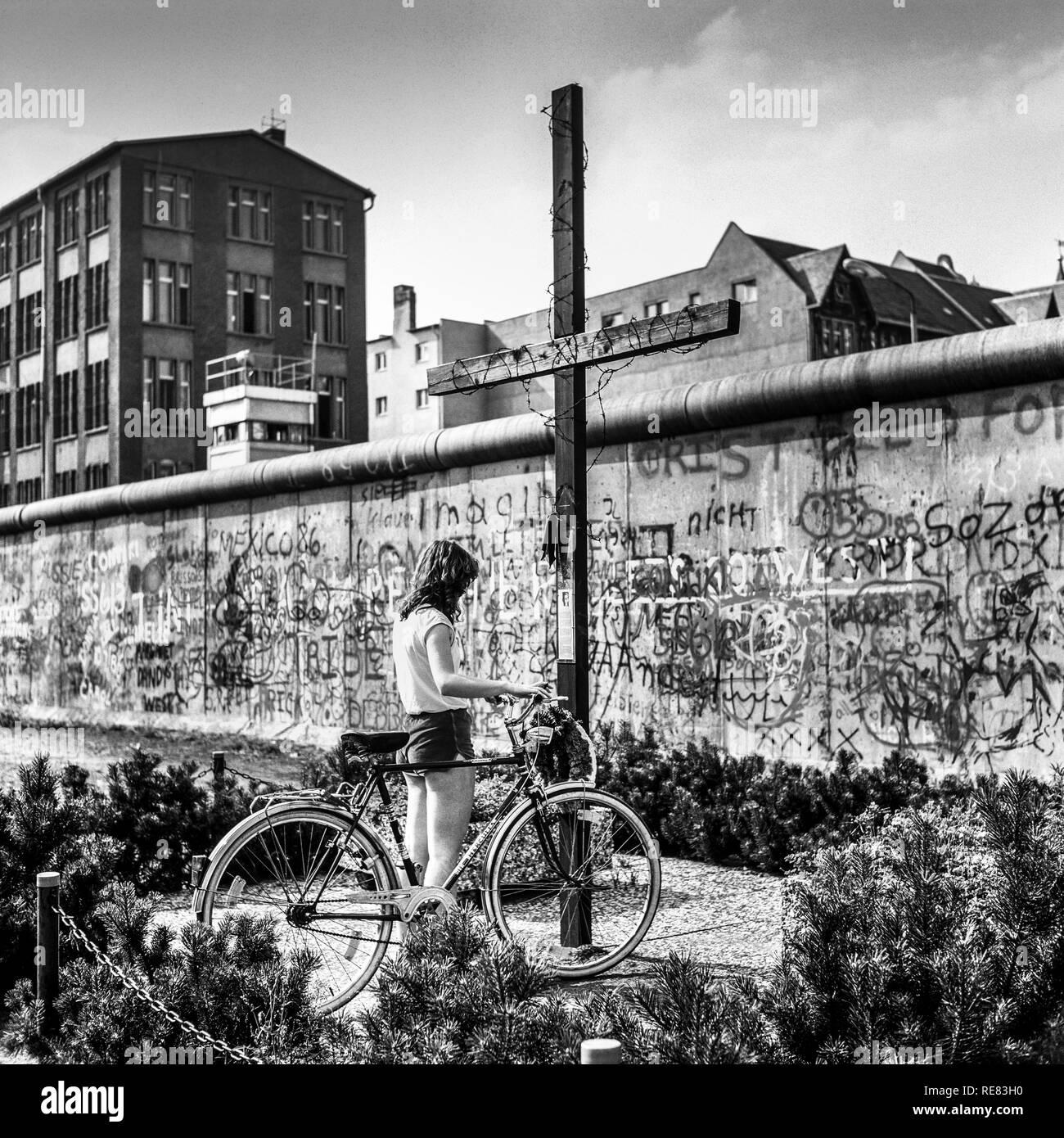 August 1986, young woman with bike, Peter Fechter memorial, graffitis on Berlin Wall, Zimmerstrasse street, Kreuzberg, West Berlin, Germany, Europe, - Stock Image