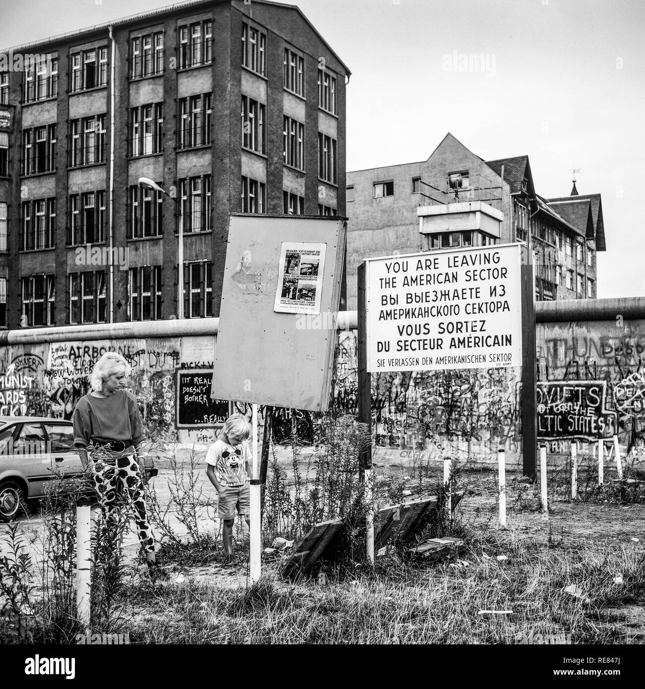 August 1986, woman and boy, leaving American sector warning sign, Berlin Wall graffitis, Zimmerstrasse street, West Berlin side, Germany, Europe, - Stock Image