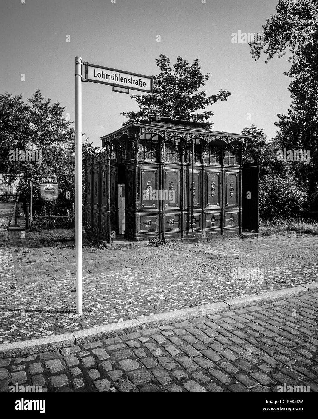 August 1986, ancient public toilet 1899, Lohmühlenstrasse street sign, Treptow, West Berlin side, Germany, Europe, - Stock Image