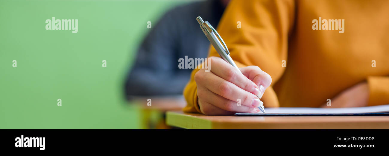 Students taking exam in classroom. Education test and literacy concept. Cropped shot, hand detail. - Stock Image