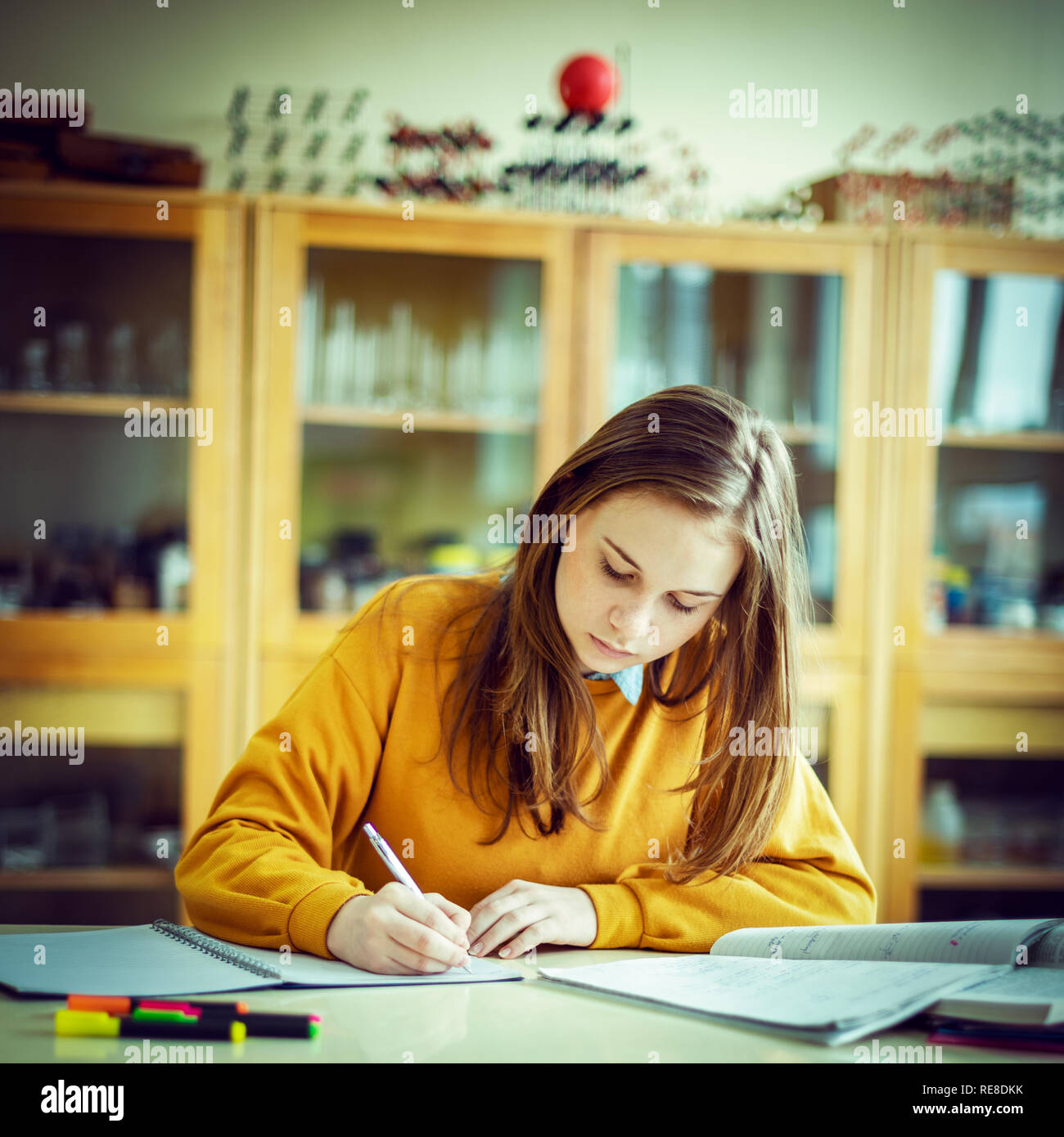 Young female college student in chemistry class, writing notes. Focused student in classroom. Authentic Education concept. Stock Photo