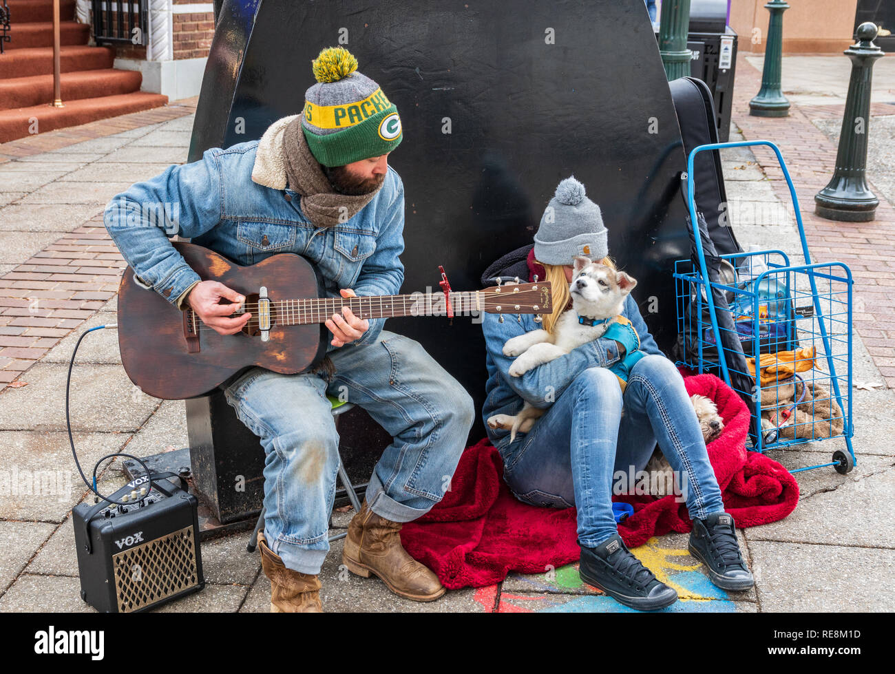 ASHEVILLE, NC, USA-1/18/19: A guitar playing busker, accompanied by a girl and two dogs. - Stock Image