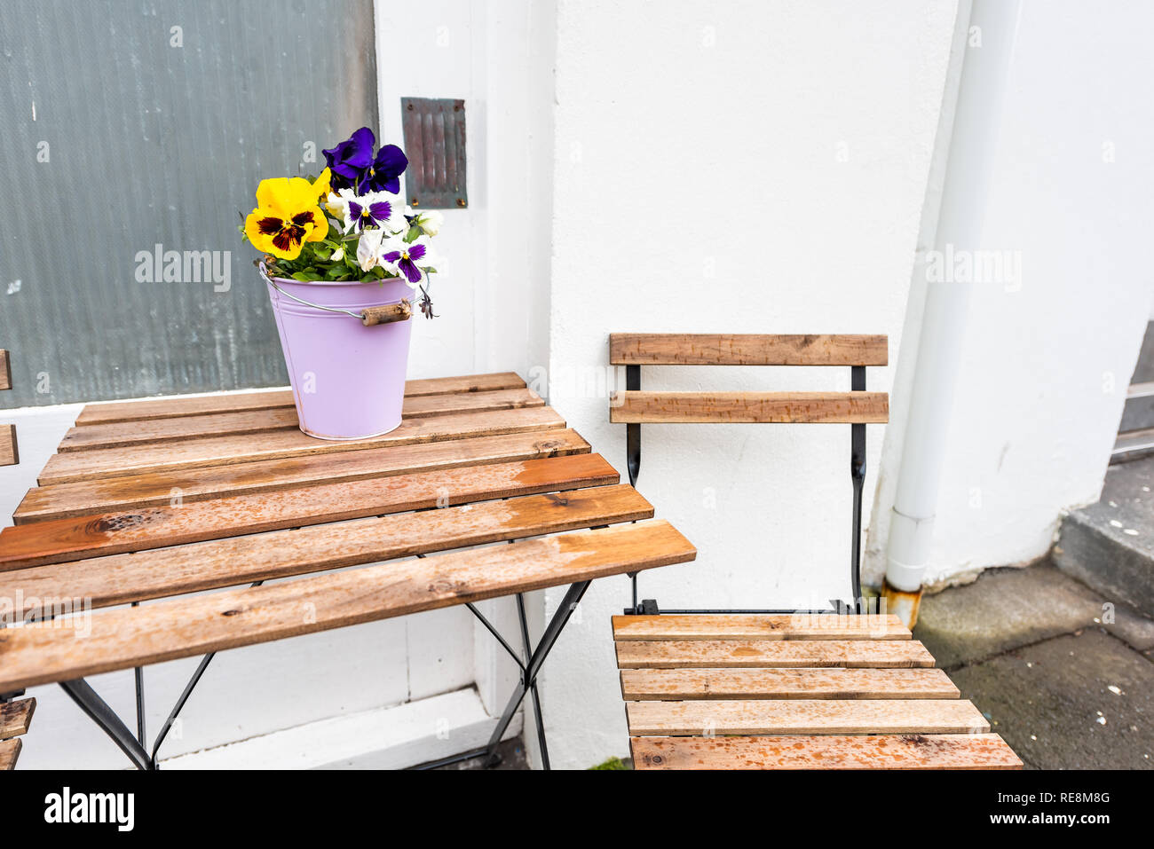 Empty wooden table outside restaurant cafe with chairs on sidewalk street and purple yellow pansy flowers in flowerpot potted plant setting with nobod - Stock Image