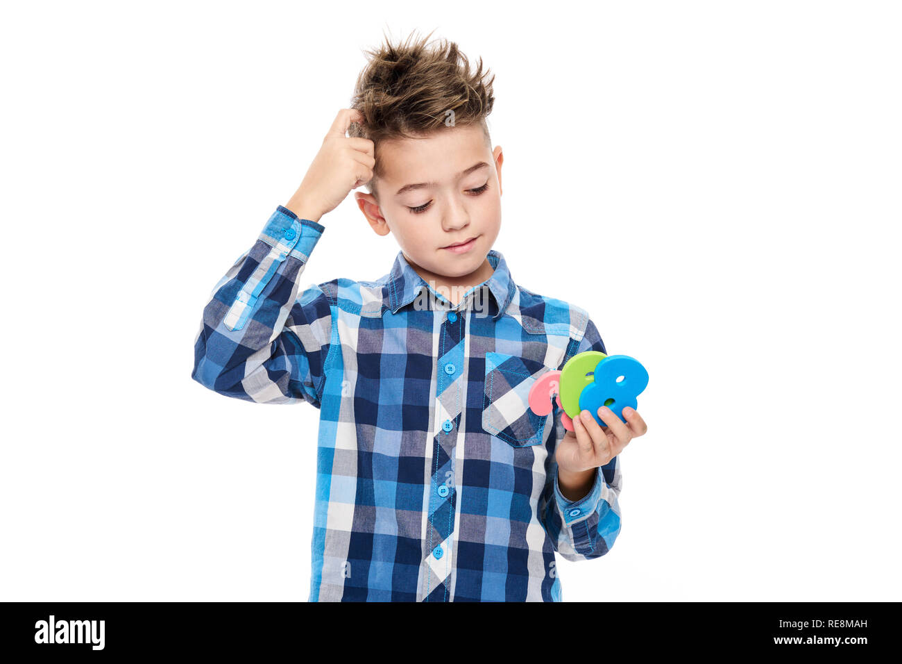 Cute boy with dyscalculia holding large colorful numbers and scratching his head. Learning disability concept on white background. - Stock Image