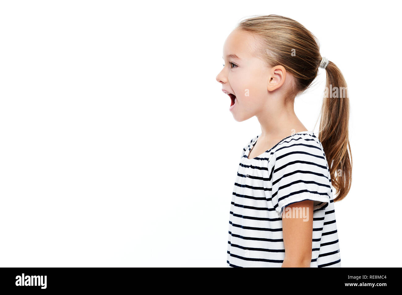 Cute little girl in stripped T-shirt talking. Speech therapy concept over white background. - Stock Image
