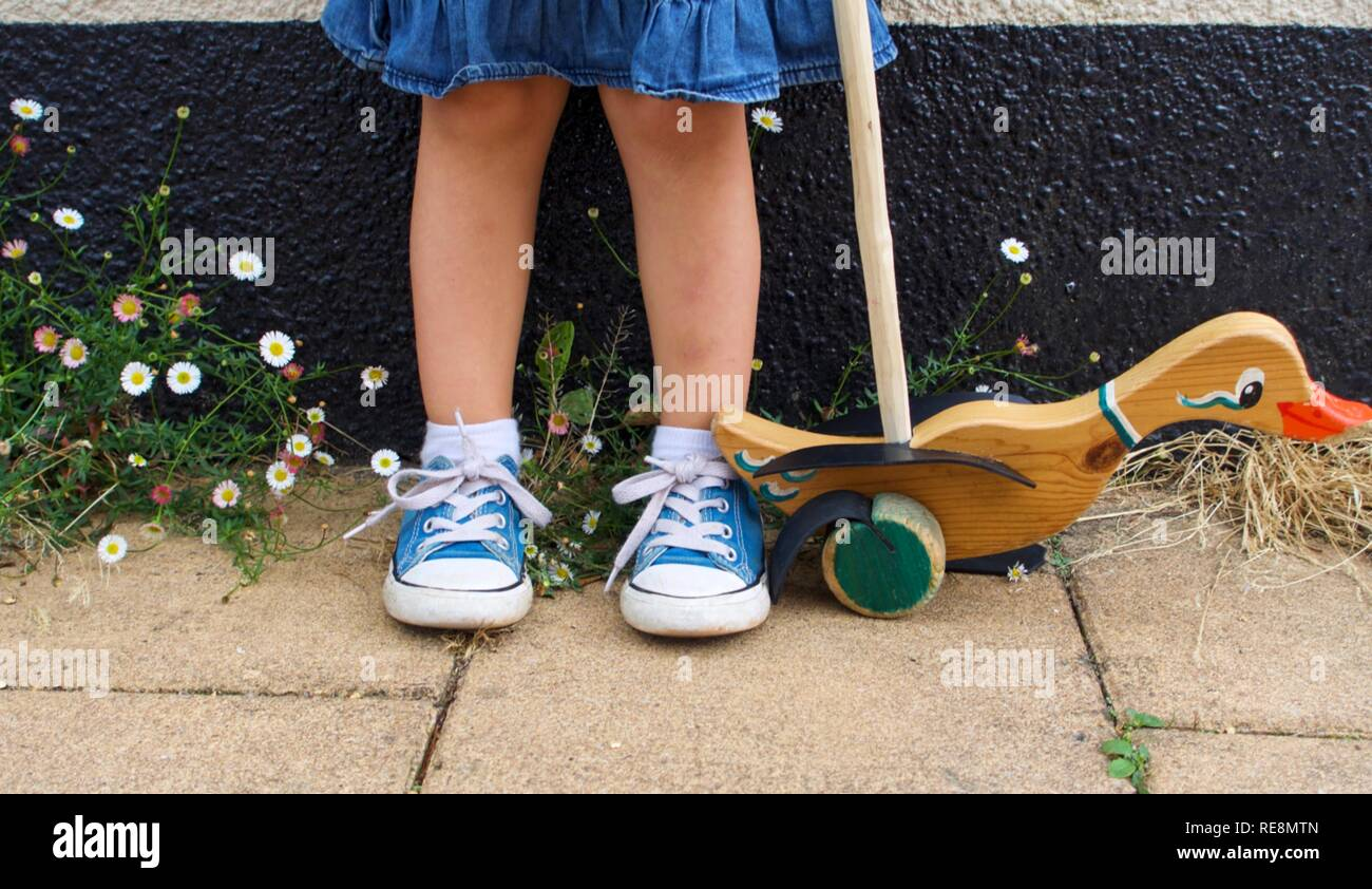 Low shot of little girl in sneakers with push along duck toy - Stock Image