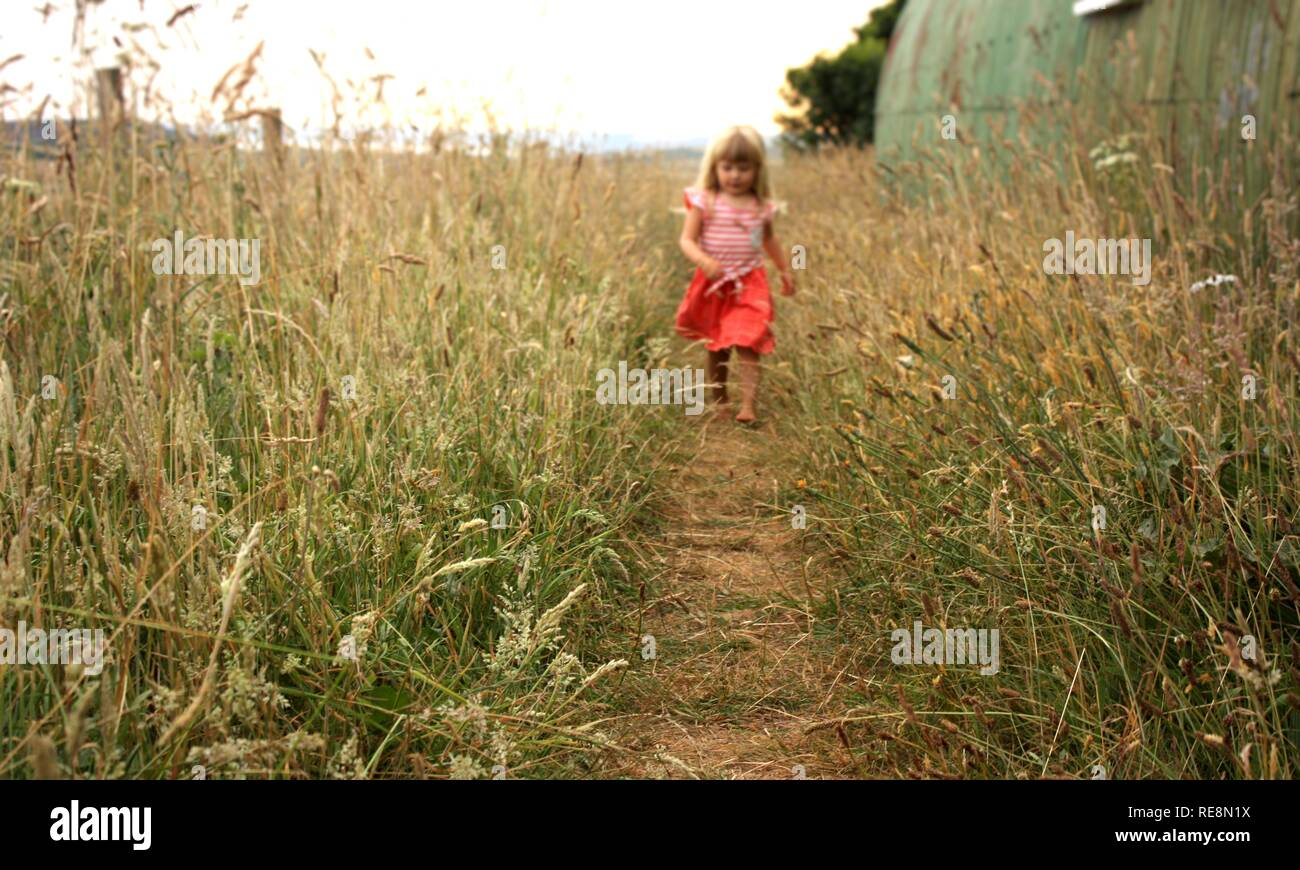 Child girl running through long grass path - Stock Image