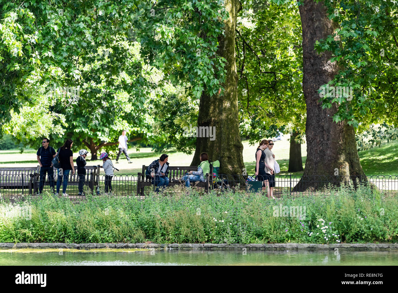 London, UK - June 21, 2018: St James Park green trees in sunny summer with many people walking on sidewalk by pond river water and sitting on benches Stock Photo