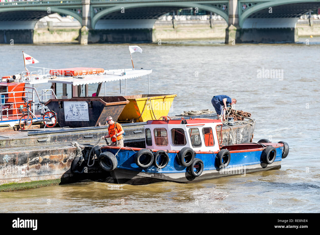 London, UK - June 21, 2018: Closeup of one industrial moored ship on Thames River water in summer sunny day with people men working cleaning from wast - Stock Image
