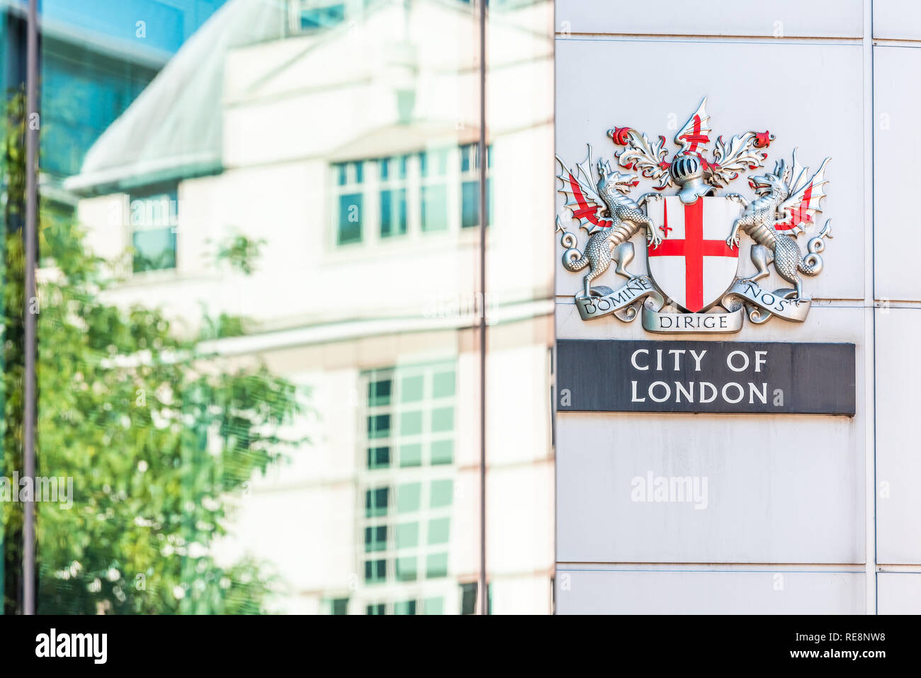 City of London, UK - June 22, 2018: Closeup of modern architecture glass window of building reflection and sign in central business downtown and nobod - Stock Image