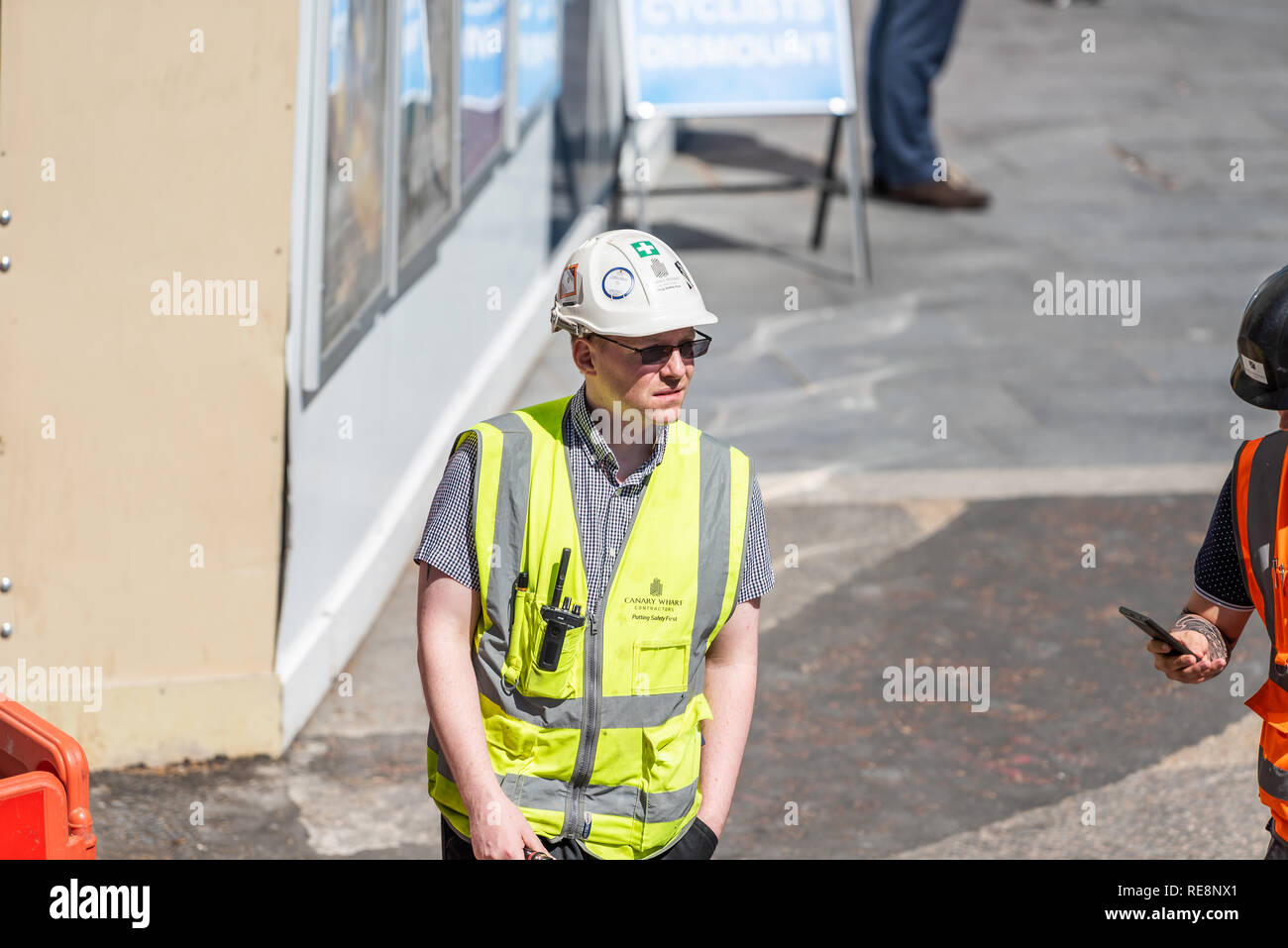 London, UK - June 22, 2018: High angle view on one construction worker, man with neon yellow green uniform vest clothing with helmet on city street - Stock Image
