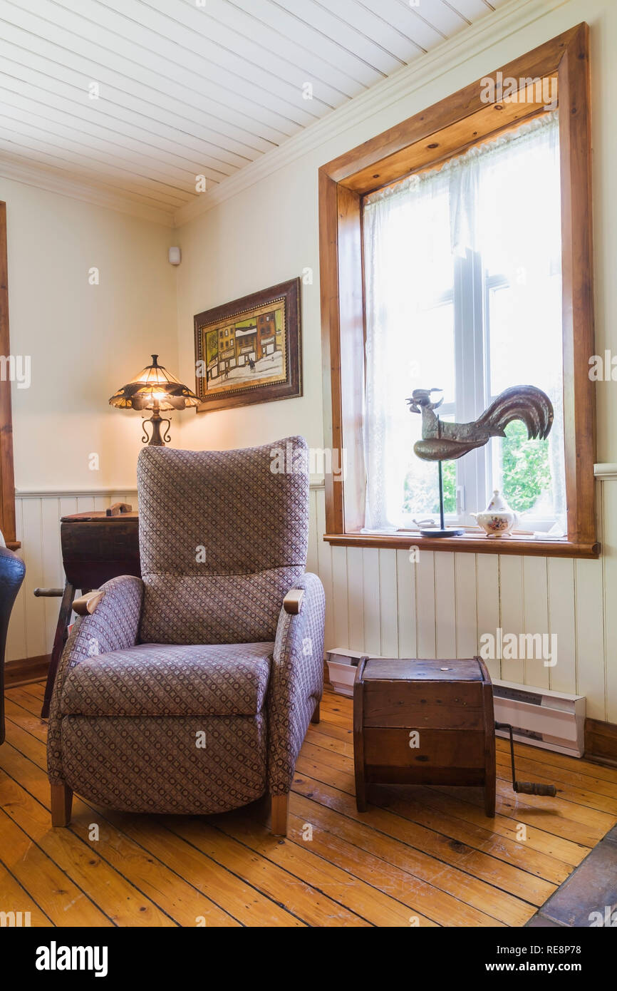 Cloth upholstered armchair in living room inside an old 1892 Canadiana cottage style home - Stock Image